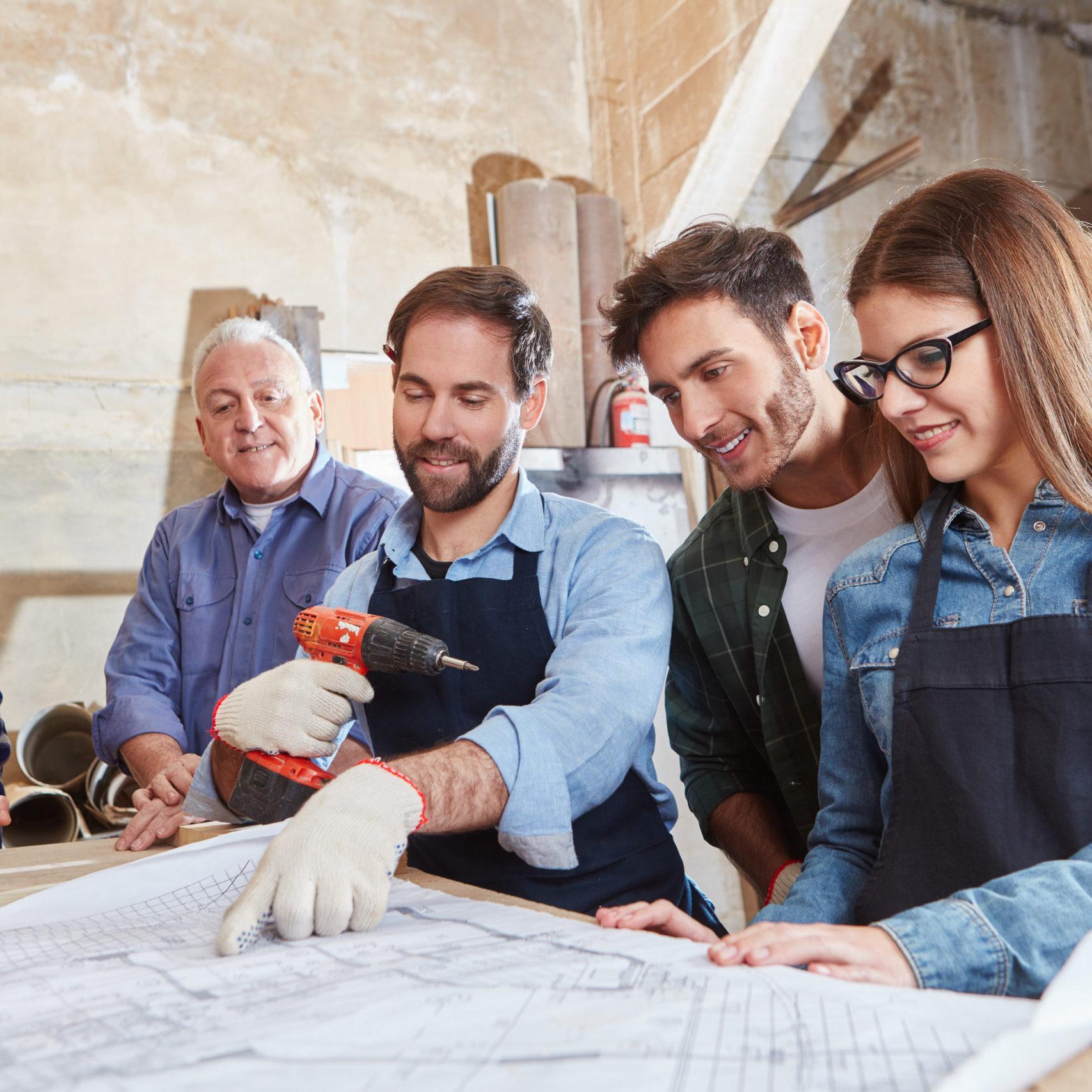 Handwerker Team arbeitet zusammen an Bauplan in Schreinerei